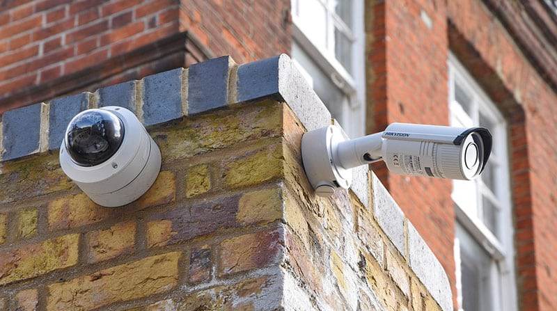 image of two CCTV cameras mounted on the external brick wall of an office building